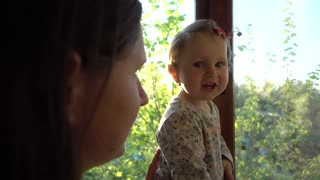 Mom and little Girl standing looking through the Window on the sunny Street
