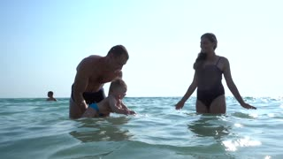 Mom & Dad play with their little Boy in a Water learn to swim on Sunset Summer Sea Beach