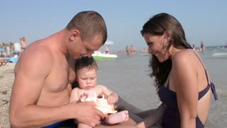 Mom & Dad play with their little Boy in a Water on Sunset Summer Sea Beach