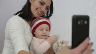 Mom with Mobile Smart Phone Pictures Selfie of little Baby Girl in hands, Studio