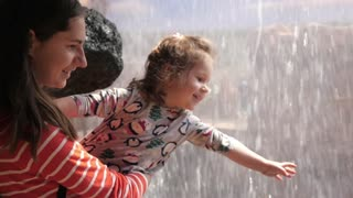 Mother and little child Girl play with Waterfall touching Water by Hand