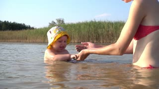 Mother and little Child Girl Swim and Play in the Lake Water in Summer Day