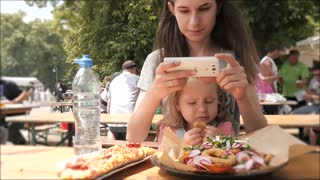 Mother make Photo with Phone - Child Daughter Eating A Salad and Potato Outdoors
