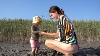 Mother puts medical natural clay on the skin of her little daughter on the lake