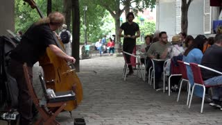 Musician playing the cello for people of cozy street cafe Montmartre Paris