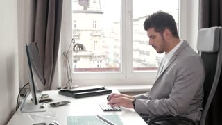 Office Man working with Computer pc, grey Suit, bright Office