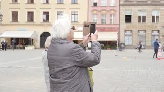 Old Senior Lady Tourist make Photo with Smart Phone on the City Street