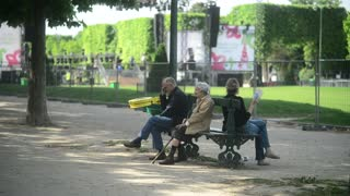 Old senior People relaxing sitting Champs-de-Mars Paris evening