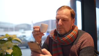 Older senior Man use Mobile Smart Phone sitting at the Table Cafe by the Window