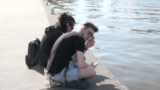 Outdoors Portrait Of Two Boys Friends Using Mobile Phone on City Quay