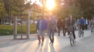 Pedestrian walking and riding Bicycles in a City Park in Evening Yellow Sun