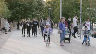 Pedestrian walking Family riding Bicycles in a City Park in Evening Yellow Sun