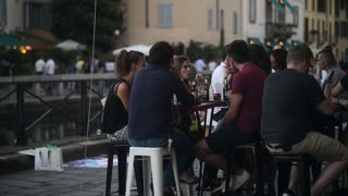 People eat and drink sitting at the Tables Cafe Restaurant Milan Naviglio Grande