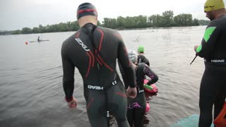 People in Rubber Suits go to the River Water for swimming Training