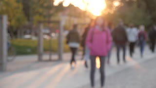 People Pedestrian walking in a City Park in Evening Yellow Sun, out of Focus