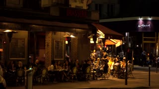 People sit relax by the tables of cozy street cafe Montmartre Paris Night