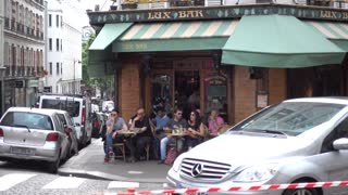 People sit relax eating meals by the tables of cozy street cafe Montmartre Paris