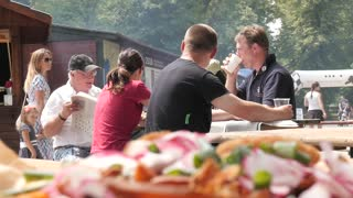 People sitting eating, drinking and talking on Street Food Festival - Summer Day