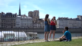 People sitting relax near Seine in Paris - romantic place in summer day