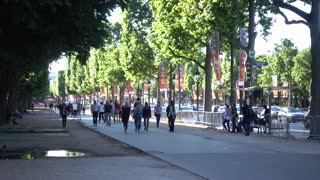 People walk along Champs Elysees sidewalk in Paris