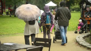 People walk under Umbrellas in a Park under the Rain - Wroclaw, Poland