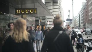 People walking by Gucci Shop on Friedrichstrase Street in Berlin - Autumn day