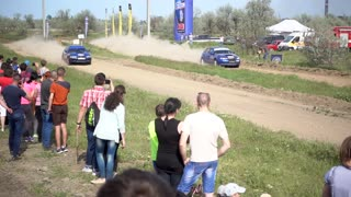 People watching Car race show with Dust Clouds rising