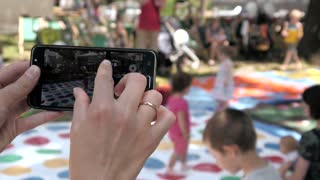Person make Photos with Mobile Smart Phone in public Place with Crowd of People
