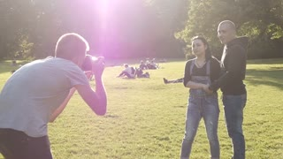Photographer work with Young Couple in the Park - romantic Photo Session