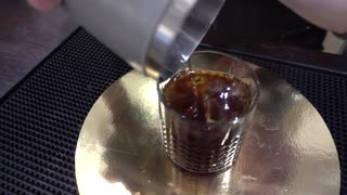 Pouring ice cube into Coke Soda