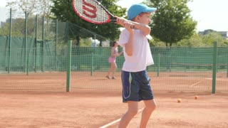 Rich Kid Boy playing Tennis on a Cort with his Father