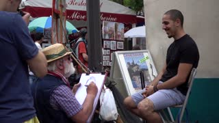 Street artist paints a portrait of a young man - Montmartre Paris
