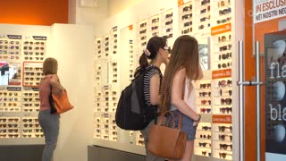 Sunglasses and Glasses in Boutique. Young woman shopping in Milan Italy