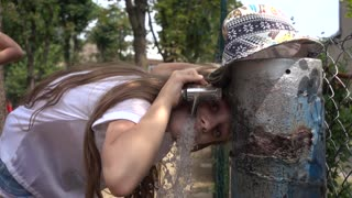 The girl drinks water from the column on a hot summer day
