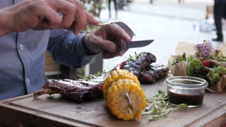 The Man cut off a piece of Pork Ripe Meat with a Knife and a Fork, Street Table