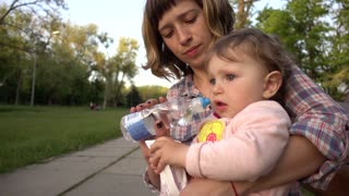Thirsty Child Drinking Water On Bench In Park, Sitting with Mom