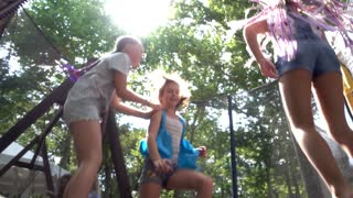 Three girls jump and have fun at the Trampoline on a Playground Summer Day