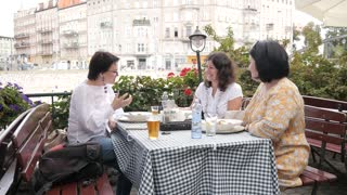 Three women Tourists sitting in a outdoors Restaurant in old European City