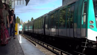 Train of Paris subway arrives at the station with passengers