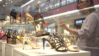 Transgender Gay with Make up on Face on a Shopping - Elegant shoes in showcase of boutique in a Mall business center
