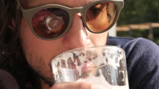 Trendy Latin Man drinking Beer in a Street Restaurant Mexican - sunny Day