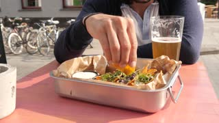 Trendy Latin Man eating Nachos with Beer in Street Restaurant Mexican, sunny Day