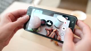 Trendy Woman In A Restaurant Make Photo Of Food With Mobile Phone Camera