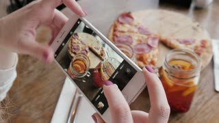 Trendy Woman With Mobile iPhone Camera In a Pizzeria Make Photo Of Food Pizza