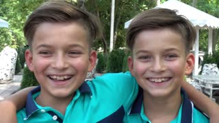 Twin Boys Smile to The Camera on the Playground Summer Day