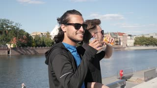 Two Boys Friends drinking Soda from metal Cans on a City Quay - Hot Summer Day
