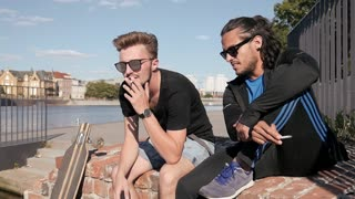 Two Boys Friends smoking Cigarettes on a City Quay - Hot Summer Day