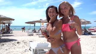 Two girls Drink Cocktails Have Fun Crazy Laughing on the Sea Summer Beach