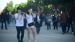 Two Korean girls take Photo via Mobile Cell Phone on Champs Elysees in Paris