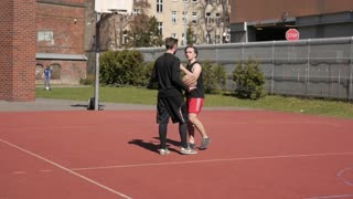 Two men guys get angry quarrel on a street basketball ground
